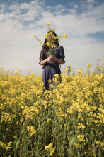 Conceptual Portrait Of A Girl In Blue Dress  Standing In A Field Of Yellow Mustard Seed Or Rapeseed Flowers Holding A Bouquet In Front Of Her Face