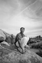 Man Crouching Down On Boulder In The Desert