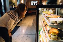 Woman Choosing Desserts In Bakery