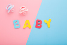 Two Silicone Soothers And Baby Word Created From Colorful Letters On Light Pink Blue Table Background. Pastel Color. Closeup. First Girls And Boys Toy. Top Down View. Two Sides.