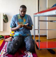 Black Muslim Praying At Home.