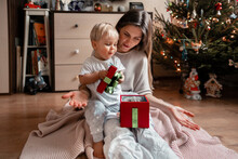 Young Mother With Baby Looks At The Christmas Decor.