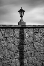 A Garden Lamp With The Straight Shadow Of A Street Lamp.