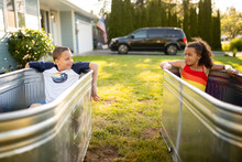 Siblings Relax In Stock Tank Pools