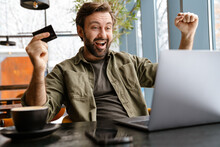 Excited Man Making Winner Gesture While Using Credit Card And Laptop