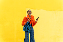 Young Trendy Woman Standing In Front Of Yellow Wall Holding Phone And Laughing Looking At Camera
