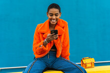 Young Trendy Woman Looking At Phone And Laughing Sitting On Top Of Wall