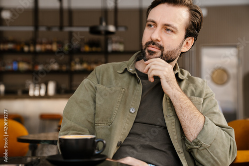 Tela Unshaven serious man looking aside while sitting and drinking coffee