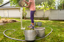 Child Dumps Out Bucket Of Water In Yard