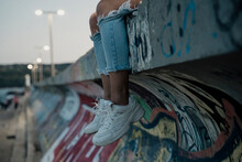 Detail Of Legs And Shoes Hanging From Wall Young Stylish Woman Sitting On Top Of Wall With Graffity With Cool Attitude