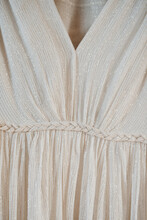 Closeup Of An Amazing White Silk Wedding Dress With Gold Details