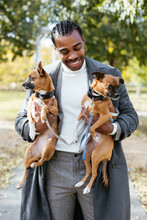 Cheerful Black Male Owner Hugging Dogs In Park