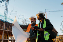 Woman Engineer Supervising Construction Of Building With Construction Worker At Sunset.