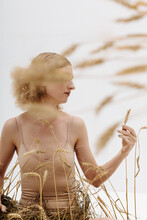 Fair Haired Woman Among Dried Plants