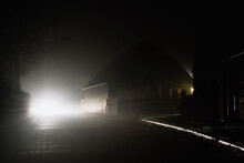 Car Headlights On A Country Road Next To Farm Buildings
