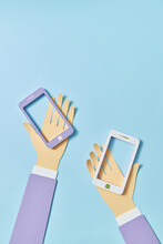 Two Craft Smartphones In Two Paper Hands.
