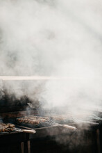Roasting Meat On A Barbecue With Loads Of Smoke