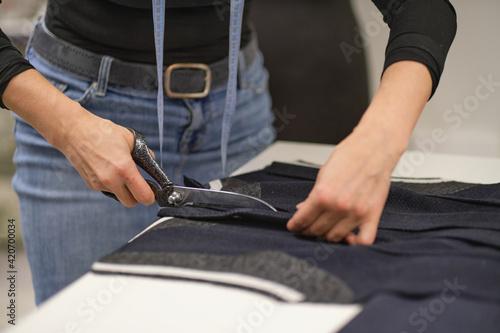 Tela Dressmaker cutting dress fabric on sketch line