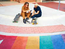 Gay Friends Using A Phone After Skating In The City.