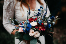 Bride Holding Amazing Wedding Bouquet With Red, Pink And Blue Tones