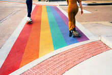 Pride. A Couple Of Gay Friends Rolling Longboard On Heels Boots Over A Rainbow Flag Crosswalk.