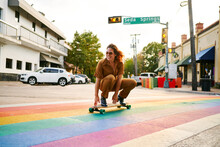 Young Girl Skating Over A Pride Flag Crosswalk.