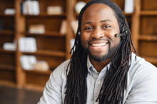African American Operator With Long Dreadlocks And Headset, Looking At Camera, Working In Callcentre On Support Hotline In Modern Office With Copy Space, Portrait Of Positive Agent In Conversation