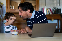 Daughter Giving Cereals To Her Father While He Works On The Laptop At Home