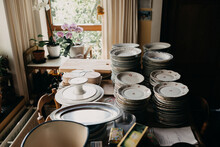 Antique Porcelain Plates Stacked On A Wooden Table Together With Other Kitchen Utilites