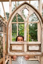 Girl Peeking Through Old Church Window Frame