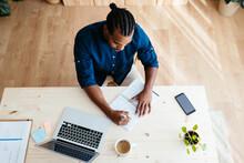 Black Freelancer Making Notes At Table