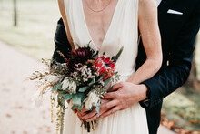 Bride And Groom Holding A Beautiful Wedding Bouquet With White And Red Details