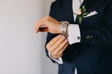 Man In Suit Adjusting Watch