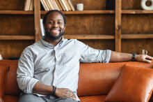 Ethnic Black Unshaved Plump Man With Dreadlocks Sitting On The Leather Sofa And Smiling, In A Normal Blue Shirt And Jeans, Feeling Comfort And Relaxation, At An Interview, Bookcase In The Background