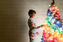 Girl In Pajamas Looks At Rainbow Tree