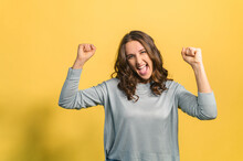 Happy And Amused Young Curly Brunette Woman Celebrating Victory, Looks At The Camera And Yelling Happily, Raised Clenched Fists In Yes Gesture, Triumph Concept, Isolated On Yellow