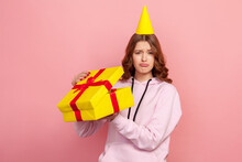 Portrait Of Displeased Young Female In Hoodie And Party Hat Opening Birthday Gift On Holiday Celebration, Looking Disappointed. Indoor Studio Shot Isolated On Pink Background