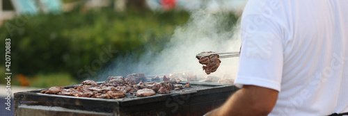Fototapeta Chef removes fried hot cuts of meat with tongs from grill and places in plate. obraz