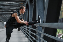 Male Athlete Stretching Legs On Bridge