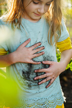 Girl Wiping Muddy Hands On Her Shirt