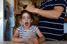 Father Combing His Daughter While She Is Yawning At Typical Andalusian House