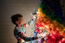 Smiling Girl Adds Lights To Christmas Tree