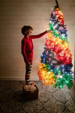 Boy In Pajamas Decorates Rainbow Tree
