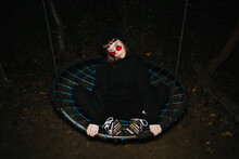 Young Girl In Red Glasses On A Swing