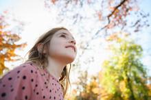 Girl Looking Upwards Towards Trees