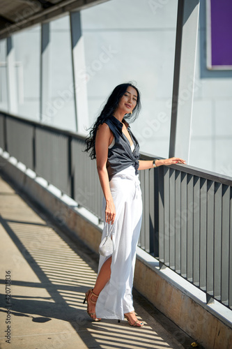 Outdoor fashion portrait of young woman posing in the corridor Fototapeta