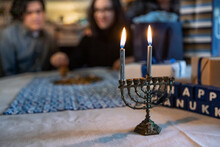 Hanukkah: Menorah With Family Playing Dreidel In Background