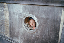 Child Looks Out Of Small Window