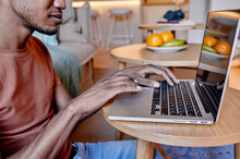 Man Using A Laptop On His Living Room Floor