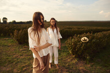 Young Women Models Posing In Boho Style Clothes In The Rays Of The Sunset On A Rural Field.